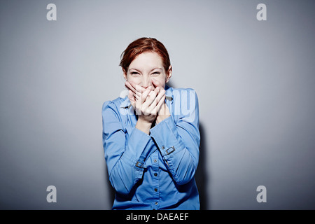 Studio portrait of young woman giggling - Stock Photo