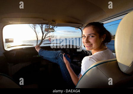 Young woman in camper van with feet up - Stock Photo