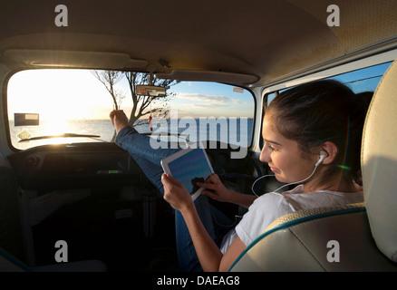 Young woman in camper van using digital tablet - Stock Photo