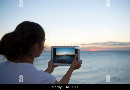 Young woman photographing with her digital tablet at sunset - Stock Photo