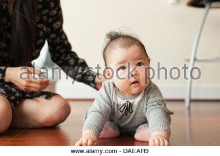 Baby girl sitting on floor - Stock Photo