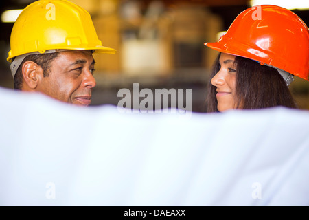 Man and woman in warehouse holding blueprint - Stock Photo