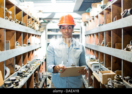 Young woman in warehouse with clipboard - Stock Photo