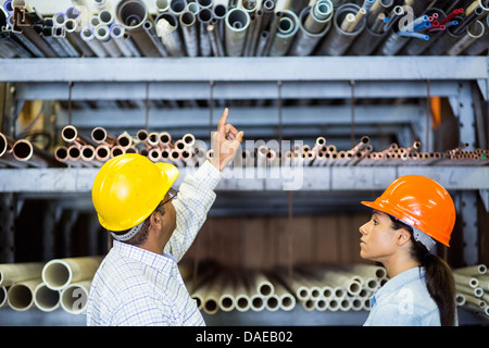 Two warehouse workers in front of shelves - Stock Photo