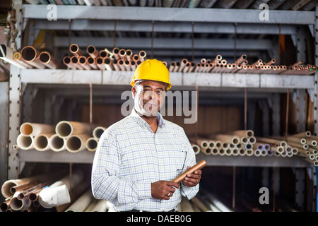 Man in warehouse with copper pipe - Stock Photo