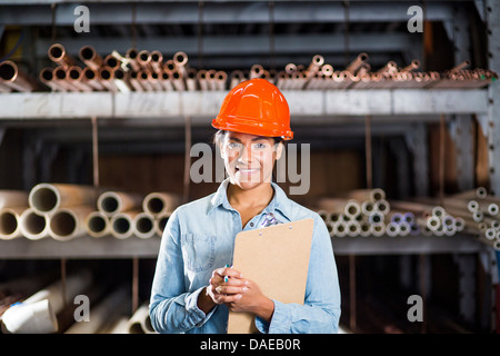 Portrait of woman in warehouse with clipboard - Stock Photo
