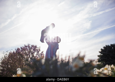 Grandfather holding up baby girl in garden - Stock Photo