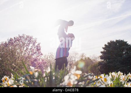 Grandfather holding up granddaughter in garden - Stock Photo