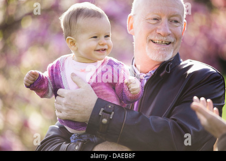 Close up portrait of baby girl and grandfather - Stock Photo