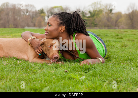 Young woman and her dog lying on grass - Stock Photo