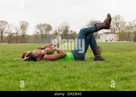Young woman and her dog playing on grass - Stock Photo