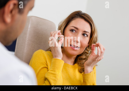 Patient explaining symptom to doctor in hospital - Stock Photo