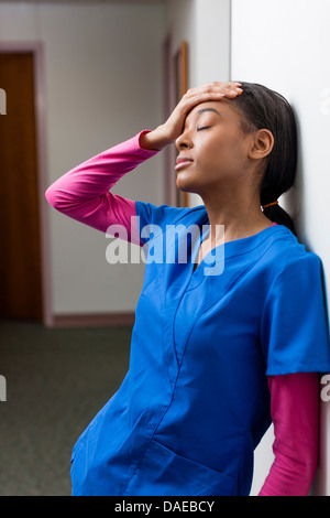 Nurse with eyes closed and hand on head in hospital corridor - Stock Photo