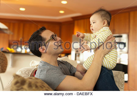 Close up of father sitting on sofa with baby daughter - Stock Photo