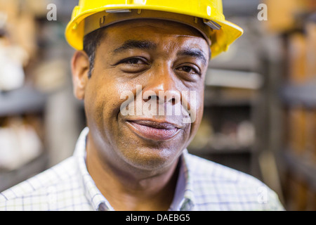 Close up portrait of man in stockroom wearing hard hat - Stock Photo