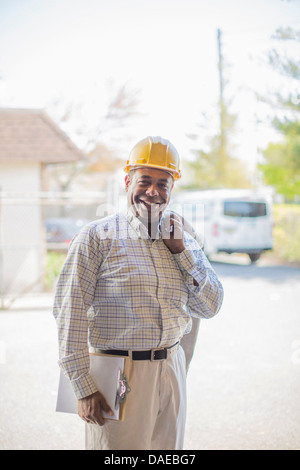 Portrait of man wearing hard hat and carrying clipboard - Stock Photo
