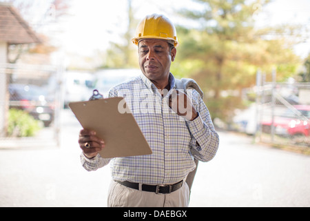 Man wearing hard hat looking at clipboard - Stock Photo