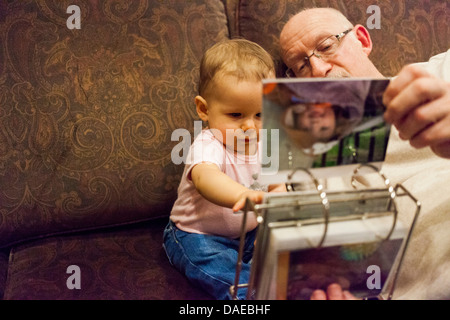 Grandfather and baby granddaughter looking at photo album - Stock Photo