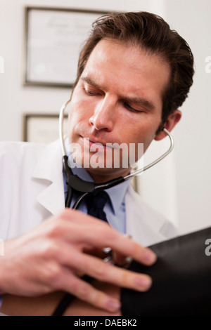 Mid adult doctor using stethoscope and blood pressure cuff on patient, close up - Stock Photo