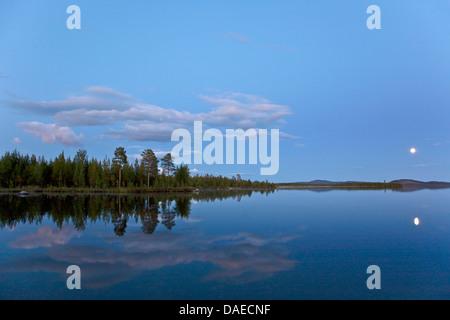 full moon mirroring in a lake in evening light, Sweden, Lapland, Norrbottens Laen, Kvikkjokk - Stock Photo