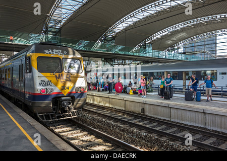 Tourists with suitcases and backpackers on vacation waiting on platform for train at railway station during the - Stock Photo