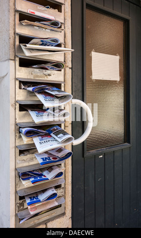 Mailboxes of apartment filled with advertising papers - Stock Photo