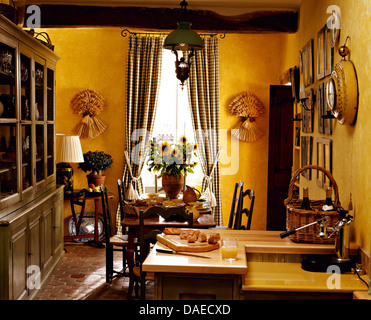 Large painted dresser in bright yellow French country kitchen dining room with checked curtains on the windows - Stock Photo