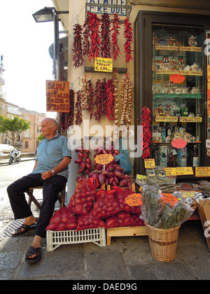 old man sitting in front of a store, Italy, Calabrien, Tropea - Stock Photo