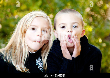 Boy and Girl Making Funny Faces - Stock Photo