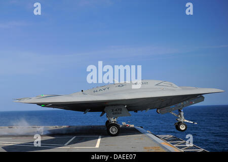 A US Navy X-47B unmanned combat air system drone launches from the flight deck of the aircraft carrier USS George - Stock Photo