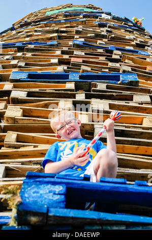 Belfast, Northern Ireland, 11th July 2013 - Six year old Nathan Sterrett climbs up Shankill Road bonfire Credit: - Stock Photo