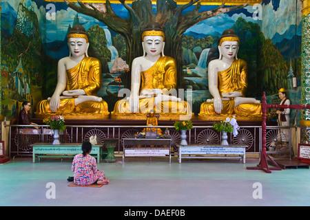 woman sitting in front of three Buddha Statues at Shwemawdaw Paya, Burma, Bago - Stock Photo
