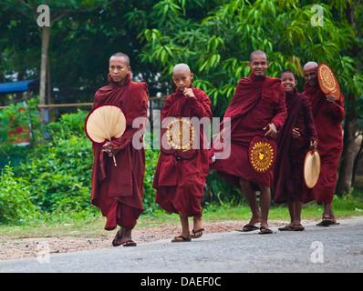 buddhistic monks walking along the road, Burma, Bago - Stock Photo