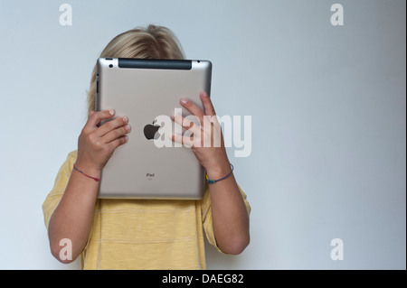 Concept/Infant boy at home with his head buried in his Apple iPad tablet computer - Stock Photo