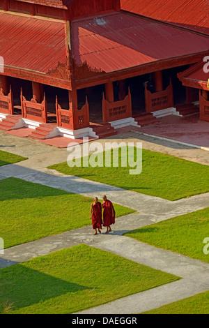 two young monks walking on a path between buildings of Mandalay Palace, Burma, Mandalay - Stock Photo