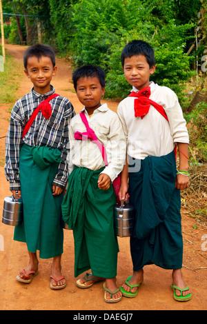 three school boys on their way to school near the Inle Lake, Burma - Stock Photo
