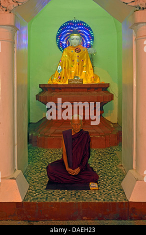 old monk sitting meditating in front of a Buddha statue at the Shwedagon Pagoda, the most important sacral building - Stock Photo