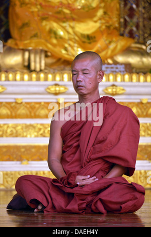 monk sitting meditating in front of a Buddha statue at the Shwedagon Pagoda, the most important sacral building - Stock Photo