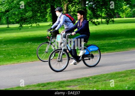 Two men riding bicycles in Kensington Gardens, London, UK - Stock Photo