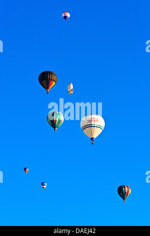Wide-angle shot of many colorful hot air balloons against clear blue sky at sunrise at Spirit of Boise Balloon Classic - Stock Photo
