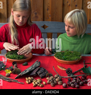 two children tinkering a dwarf garden with nature materials, Germany - Stock Photo
