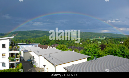 panoramic view over the roofs of a housing estate at a rainbow over forested hill landscape, Germany, North Rhine - Stock Photo