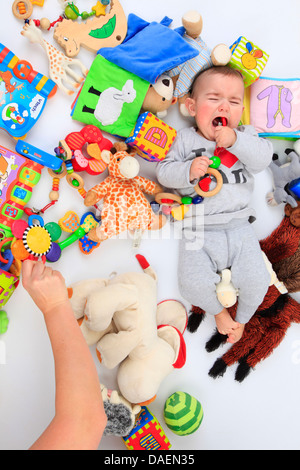 weeping baby lying between toys - Stock Photo
