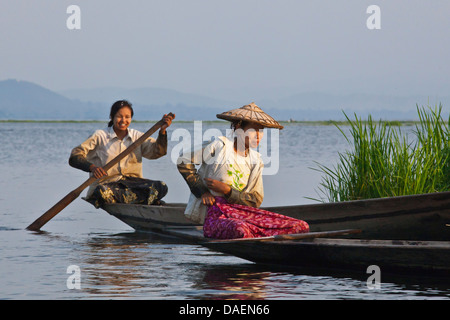two women sitting in tailor seat in handmade wooden boats on the Inle Lake, Burma - Stock Photo
