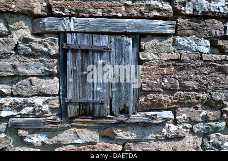 Weathered door at a window by an old brick wall. - Stock Photo