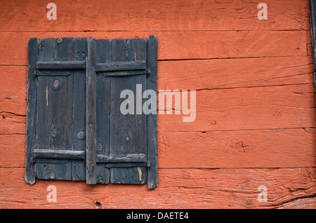 Black old wooden doors at a red wall - Stock Photo