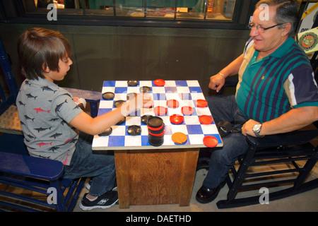 Miami Florida City Florida Cracker Barrel Old Country Store restaurant man grandfather boy grandson playing checkers - Stock Photo