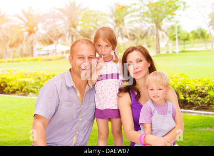 Portrait of cute family in spending time together in the park, happy young parents with two adorable child outdoors - Stock Photo
