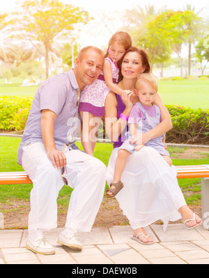 Cute family sitting on bench in the park, active lifestyle, little brother and sister with parent outdoors, parenthood - Stock Photo