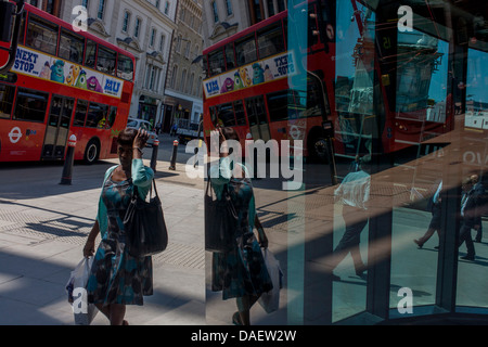Londoners seen reflected in multiple plate glass windows on a busy summer lunchtime, in the Square Mile, the capital's - Stock Photo